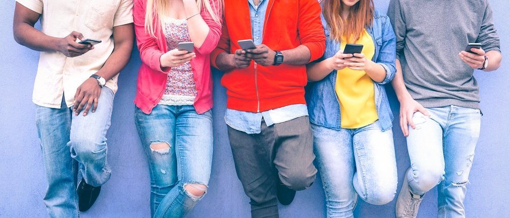 Young people using social media on their phones